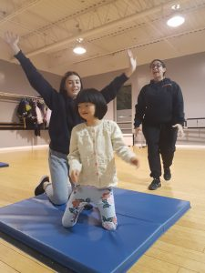 Teacher supervising little girl and a female volunteer who are dancing on a mat.