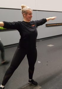 Kayla, instructor, stretching arms out
