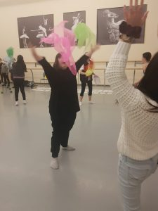 Girl happy dancing with pink and green scarfs