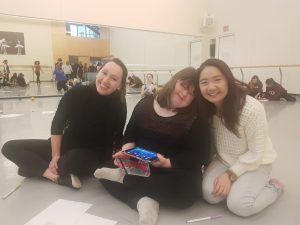 Three women sitting on a dance studio floor and smilling. The one in the middle is holding and iPad.