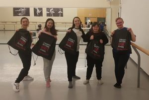 Five dancers smiling and holding Canada's National Ballet School bags